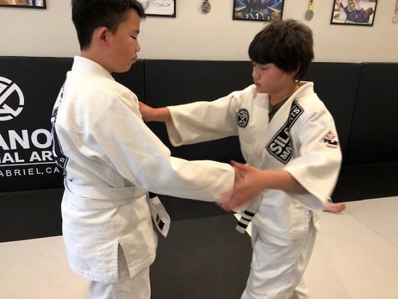 Jaelan working his Jiu-Jitsu takedown game with his training partner in the Kids 2 program at Silanoe.