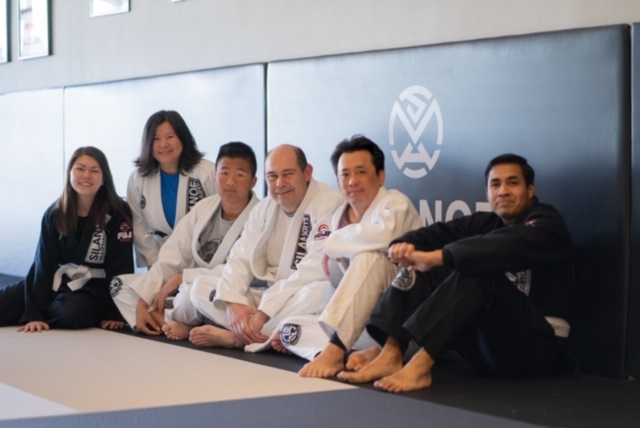 The students of the Saturday morning BJJ All Levels class lined up against the mat wall at Silanoe