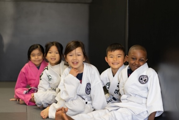 Chelsea, Alayna, Hazel, Colin and Tony from our Kids 1 BJJ program are seated against the wall looking into the camera.