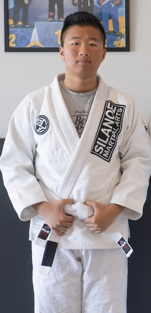 Kalani in a white BJJ gi in front of the picture wall at the San Gabriel Alhambra adjacent Silanoe Martial Arts location.