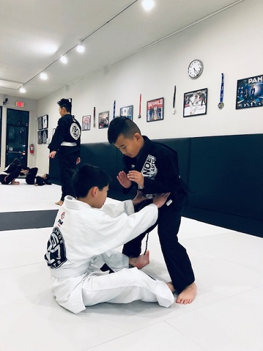 Caleb practising the Dummy Sweep in the BJJ Kids Class with Devon