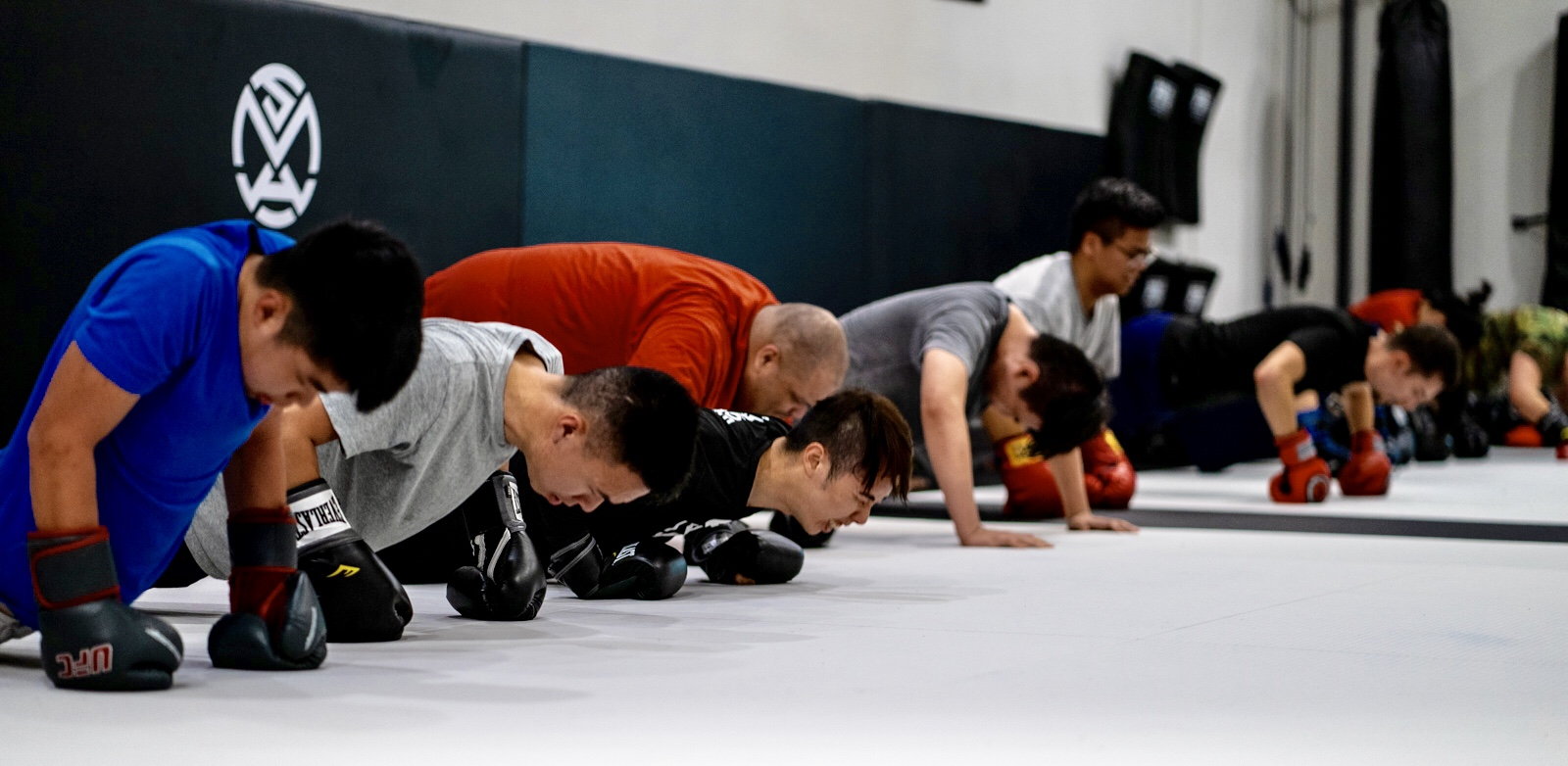 Joe Hernandez in pushup stance with Kickboxing Muay Thai teammates at Silanoe San Gabriel Alhambra adjacent
